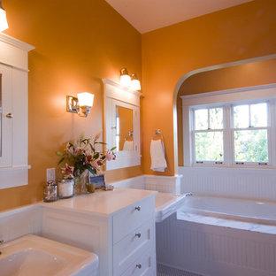 シアトルの中サイズのトラディショナルスタイルのおしゃれなマスターバスルーム (ペデスタルシンク、白いキャビネット、アルコーブ型浴槽、オレンジの壁) の写真