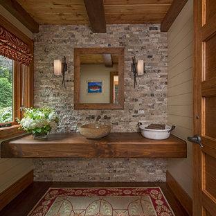Diseño de cuarto de baño rural con armarios abiertos, puertas de armario de madera oscura, baldosas y/o azulejos beige, baldosas y/o azulejos blancas y negros, baldosas y/o azulejos grises, paredes beige, suelo de madera en tonos medios, lavabo sobreencimera, encimera de madera y suelo marrón