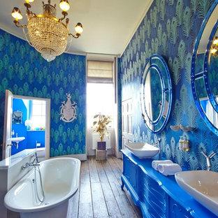 Imagen de cuarto de baño infantil, bohemio, grande, con armarios con rebordes decorativos, puertas de armario azules, bañera exenta, combinación de ducha y bañera, paredes azules, suelo de madera oscura y lavabo sobreencimera