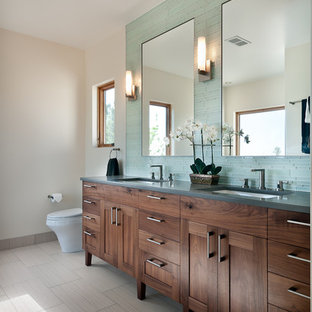 Photo of a transitional bathroom in Denver with shaker cabinets, blue tile, matchstick tile, dark wood cabinets and grey benchtops.