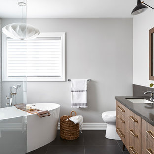 Foto de cuarto de baño actual con armarios con paneles lisos, puertas de armario de madera oscura, bañera exenta, baldosas y/o azulejos blancos, paredes grises, lavabo bajoencimera, suelo negro y encimeras negras