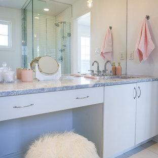 Imagen de cuarto de baño principal, escandinavo, de tamaño medio, con armarios con paneles lisos, puertas de armario blancas, bañera encastrada, ducha esquinera, sanitario de una pieza, baldosas y/o azulejos blancos, baldosas y/o azulejos de cerámica, paredes blancas, suelo de baldosas de porcelana, lavabo bajoencimera, encimera de terrazo, suelo blanco, ducha con puerta con bisagras y encimeras grises