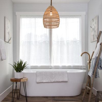 Freestanding bathtub - large cottage master porcelain tile and brown floor freestanding bathtub idea in San Francisco with gray walls