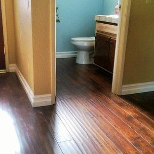 Удачное сочетание для дизайна помещения: большая ванная комната в стиле рустика с темными деревянными фасадами, синими стенами, полом из ламината, душевой кабиной, столешницей из плитки и коричневым полом - самое интересное для вас