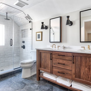Photo of a mid-sized transitional master bathroom in New York with shaker cabinets, medium wood cabinets, an alcove shower, a two-piece toilet, white tile, beige walls, porcelain floors, an undermount sink, quartzite benchtops, black floor, a hinged shower door and white benchtops.