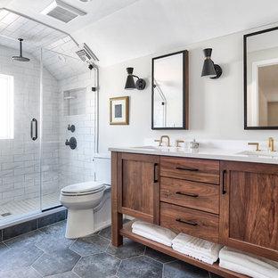 ニューヨークの中サイズのトランジショナルスタイルのおしゃれなマスターバスルーム (シェーカースタイル扉のキャビネット、中間色木目調キャビネット、アルコーブ型シャワー、分離型トイレ、白いタイル、ベージュの壁、磁器タイルの床、アンダーカウンター洗面器、珪岩の洗面台、黒い床、開き戸のシャワー、白い洗面カウンター) の写真