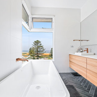 Design ideas for a large beach style master bathroom in Central Coast with flat-panel cabinets, light wood cabinets, a freestanding tub, white walls, a vessel sink, black floor, white benchtops, a single vanity and a floating vanity.