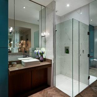 Foto på ett funkis en-suite badrum, med släta luckor, skåp i mörkt trä, bänkskiva i akrylsten, ett fristående badkar, en öppen dusch, en vägghängd toalettstol, porslinskakel, mörkt trägolv, ett fristående handfat och dusch med gångjärnsdörr