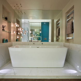Inspiration for a contemporary ensuite bathroom in London with a freestanding bath, a walk-in shower, a wall mounted toilet, porcelain tiles and dark hardwood flooring.