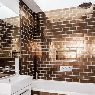 Inspiration for a contemporary bathroom in London with flat-panel cabinets, white cabinets, an alcove tub, a shower/bathtub combo, brown tile, subway tile and a console sink.