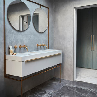 Modern bathroom in London with flat-panel cabinets, white cabinets, grey walls, an integrated sink, grey floors and white worktops.