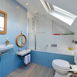 Design ideas for a beach style bathroom in London with a wall-mounted sink, an alcove bath, a shower/bath combination, a two-piece toilet, white tiles and blue walls.