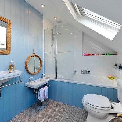 Example of a beach style white tile bathroom design in London with a wall-mount sink, a two-piece toilet and blue walls