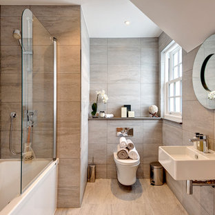 Design ideas for a classic bathroom in London with a shower/bath combination, beige tiles, stone slabs, a wall-mounted sink, an alcove bath and a wall mounted toilet.