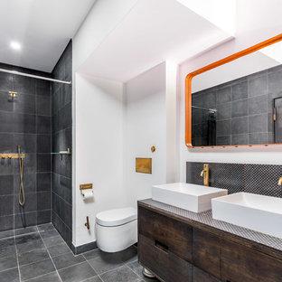 Inspiration för ett industriellt badrum, med släta luckor, skåp i mörkt trä, kaklad bänkskiva, en kantlös dusch, en vägghängd toalettstol, grå kakel, vita väggar, ett fristående handfat, grått golv och dusch med duschdraperi