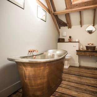 Inspiration for a country ensuite bathroom in Hampshire with medium wood cabinets, a freestanding bath, white walls, dark hardwood flooring, a vessel sink, wooden worktops, brown floors and brown worktops.