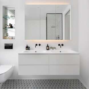 Inspiration for a scandinavian bathroom in London with flat-panel cabinets, white cabinets, white walls, an integrated sink, multi-coloured floors, white worktops and double sinks.