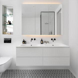Inspiration för nordiska vitt badrum, med släta luckor, vita skåp, vita väggar, ett integrerad handfat och flerfärgat golv