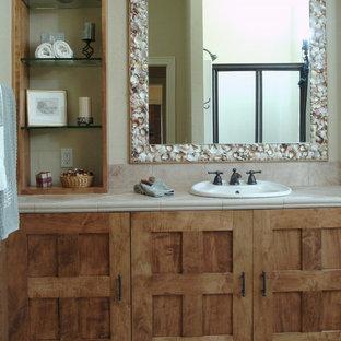 Foto på ett mellanstort maritimt badrum, med ett nedsänkt handfat, möbel-liknande, skåp i mellenmörkt trä, beige kakel, keramikplattor, beige väggar, klinkergolv i keramik, kaklad bänkskiva och beiget golv
