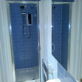 Diseño de cuarto de baño con ducha, contemporáneo, pequeño, con armarios con paneles lisos, puertas de armario blancas, ducha empotrada, sanitario de dos piezas, baldosas y/o azulejos azules, baldosas y/o azulejos de cerámica, paredes blancas, suelo de linóleo y lavabo tipo consola