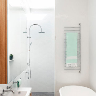 Small contemporary master bathroom in Sydney with flat-panel cabinets, medium wood cabinets, a freestanding tub, an open shower, white walls, concrete floors, a console sink, grey floor and white tile.