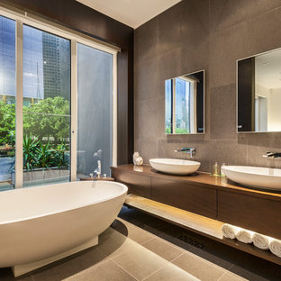 Photo of a mid-sized contemporary master bathroom in Melbourne with flat-panel cabinets, dark wood cabinets, a freestanding tub, brown tile, a vessel sink, brown floor, wood benchtops and brown benchtops.