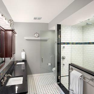 Diseño de cuarto de baño con ducha, actual, grande, con armarios con paneles con relieve, puertas de armario de madera oscura, ducha empotrada, sanitario de dos piezas, baldosas y/o azulejos blancas y negros, baldosas y/o azulejos multicolor, azulejos en listel, paredes grises, suelo de linóleo, lavabo bajoencimera y encimera de cuarzo compacto
