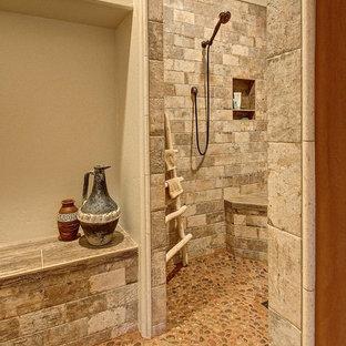 Ejemplo de cuarto de baño principal, rural, de tamaño medio, con ducha a ras de suelo, baldosas y/o azulejos de piedra, paredes beige y suelo de baldosas tipo guijarro