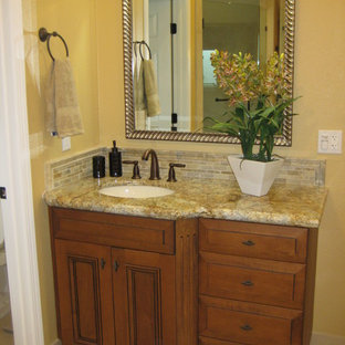 Example of a mid-sized classic master beige tile and porcelain tile porcelain tile corner shower design in San Francisco with an undermount sink, recessed-panel cabinets, medium tone wood cabinets, granite countertops, a two-piece toilet and yellow walls