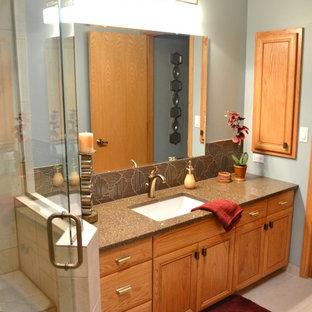 他の地域の中サイズのエクレクティックスタイルのおしゃれなマスターバスルーム (中間色木目調キャビネット、コーナー設置型シャワー、ベージュのタイル、磁器タイル、青い壁、磁器タイルの床、アンダーカウンター洗面器、クオーツストーンの洗面台) の写真
