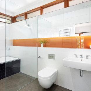 Diseño de cuarto de baño principal, minimalista, de tamaño medio, con lavabo suspendido, bañera encastrada, ducha a ras de suelo, sanitario de pared, baldosas y/o azulejos negros, baldosas y/o azulejos de cerámica, paredes blancas, suelo de baldosas de cerámica y suelo gris