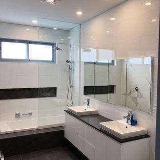 Пример оригинального дизайна: детская ванная комната среднего размера в стиле модернизм с плоскими фасадами, белыми фасадами, накладной ванной, душем над ванной, раздельным унитазом, белой плиткой, керамической плиткой, белыми стенами, полом из керамогранита, накладной раковиной, столешницей из искусственного кварца, серым полом, открытым душем, серой столешницей, нишей, тумбой под две раковины, подвесной тумбой и кессонным потолком