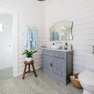Design ideas for a shabby-chic style 3/4 bathroom in Wollongong with furniture-like cabinets, grey cabinets, a curbless shower, a two-piece toilet, white walls, a vessel sink, multi-coloured floor, a hinged shower door and grey benchtops.