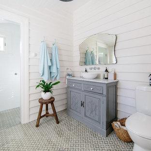 Foto på ett shabby chic-inspirerat grå badrum med dusch, med möbel-liknande, grå skåp, en kantlös dusch, en toalettstol med separat cisternkåpa, vita väggar, ett fristående handfat, flerfärgat golv och dusch med gångjärnsdörr