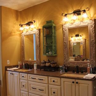 Esempio di una stanza da bagno padronale country di medie dimensioni con lavabo integrato, ante con bugna sagomata, ante beige, top in onice e pareti gialle