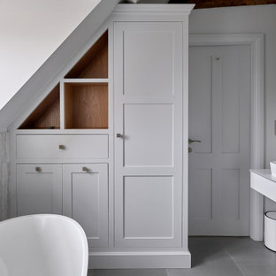 Inspiration for a small classic ensuite bathroom in West Midlands with white cabinets, a freestanding bath, grey tiles, white walls, a vessel sink, grey floors, white worktops, a single sink and a floating vanity unit.
