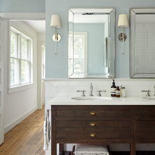 フィラデルフィアの中くらいのカントリー風おしゃれなマスターバスルーム (家具調キャビネット、ヴィンテージ仕上げキャビネット、置き型浴槽、分離型トイレ、白いタイル、セラミックタイル、青い壁、淡色無垢フローリング、アンダーカウンター洗面器、大理石の洗面台、茶色い床、開き戸のシャワー) の写真