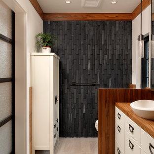 Modelo de cuarto de baño principal, de estilo zen, de tamaño medio, con puertas de armario blancas, bañera japonesa, sanitario de una pieza, suelo de baldosas de porcelana, lavabo sobreencimera, encimera de madera, armarios con paneles lisos, ducha abierta, baldosas y/o azulejos negros, baldosas y/o azulejos de piedra y paredes beige