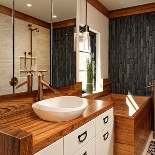 Inspiration for a mid-sized asian master bathroom in DC Metro with white cabinets, a japanese tub, porcelain floors, a vessel sink, wood benchtops, flat-panel cabinets, black tile, an open shower, a one-piece toilet, beige walls, stone tile, an open shower and brown benchtops.