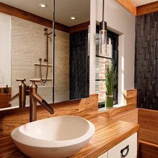 Esempio di una stanza da bagno padronale etnica di medie dimensioni con ante bianche, vasca giapponese, WC monopezzo, pavimento in gres porcellanato, lavabo a bacinella, top in legno, ante lisce, doccia aperta, piastrelle nere, piastrelle in pietra e pareti beige