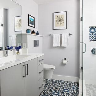 Esempio di una stanza da bagno con doccia minimal di medie dimensioni con ante lisce, ante grigie, doccia ad angolo, WC sospeso, piastrelle bianche, pareti grigie, porta doccia a battente, top bianco, lavabo integrato e pavimento blu