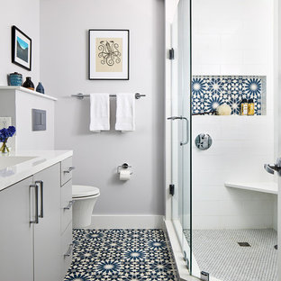 Example of a mid-sized trendy master white tile corner shower design in DC Metro with flat-panel cabinets, gray cabinets, a wall-mount toilet, gray walls, a hinged shower door and white countertops