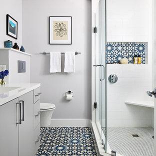 Ispirazione per una stanza da bagno padronale contemporanea di medie dimensioni con ante lisce, ante grigie, doccia ad angolo, WC sospeso, piastrelle bianche, pareti grigie, porta doccia a battente e top bianco