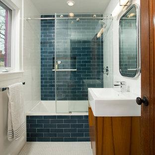 Modelo de cuarto de baño infantil, ecléctico, de tamaño medio, con armarios con paneles lisos, puertas de armario de madera oscura, bañera empotrada, combinación de ducha y bañera, sanitario de una pieza, baldosas y/o azulejos azules, baldosas y/o azulejos de cerámica, paredes blancas, lavabo sobreencimera y suelo con mosaicos de baldosas