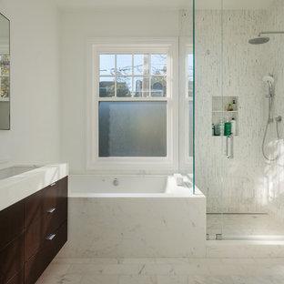 Inredning av ett modernt badrum, med ett avlångt handfat, släta luckor, skåp i mörkt trä, ett undermonterat badkar, en hörndusch och vit kakel