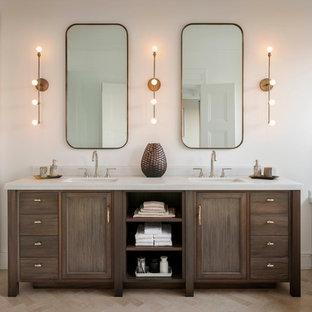 Inredning av ett klassiskt badrum, med ett undermonterad handfat, skåp i mörkt trä, ett undermonterat badkar, en dusch i en alkov, vit kakel, vita väggar och luckor med infälld panel