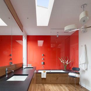 Immagine di una stanza da bagno design con lavabo sottopiano, ante lisce, ante in legno chiaro, top in saponaria, vasca sottopiano, vasca/doccia, lastra di vetro, pareti bianche, parquet chiaro e piastrelle rosse