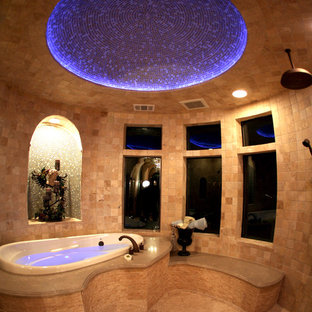 Example of a large tuscan master beige tile and mosaic tile mosaic tile floor bathroom design in Austin with a hot tub and brown walls