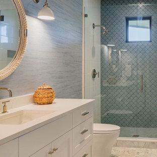 Maritimes Duschbad mit Schrankfronten mit vertiefter Füllung, weißen Schränken, Duschnische, Toilette mit Aufsatzspülkasten, blauen Fliesen, blauer Wandfarbe, Marmorboden, Unterbauwaschbecken, Quarzit-Waschtisch, weißem Boden, Falttür-Duschabtrennung, weißer Waschtischplatte, Einzelwaschbecken, eingebautem Waschtisch und Tapetenwänden in Seattle