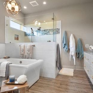 Foto på ett maritimt grå badrum, med skåp i shakerstil, grå skåp, ett fristående badkar, en hörndusch, grå väggar, mellanmörkt trägolv, ett undermonterad handfat och brunt golv